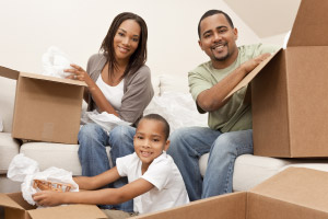 Family unpacking boxes and moving into a new home